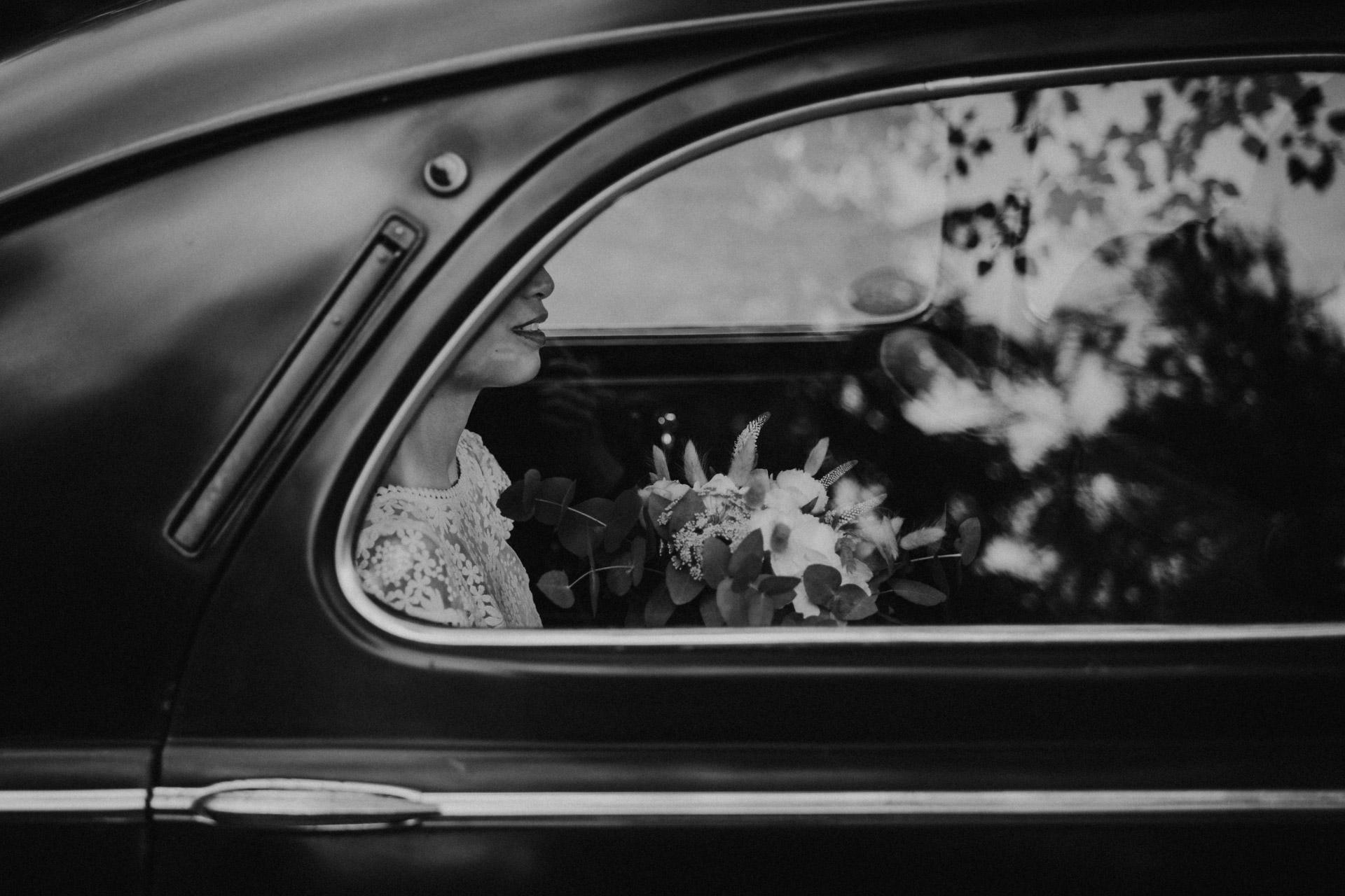 Photo noire et blanc de la mariée arrivant en voiture