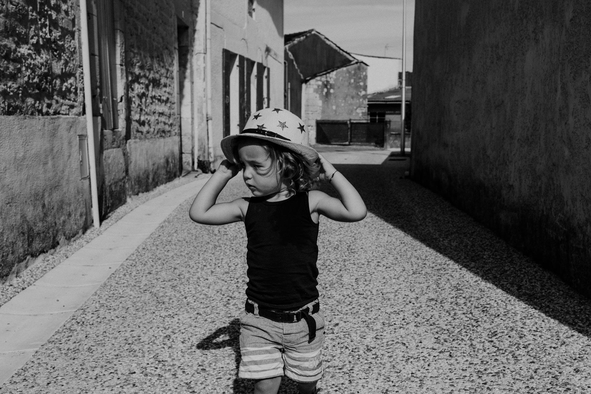 Photo noire et blanc d'un enfant dans une ruelle tenant son chapeau