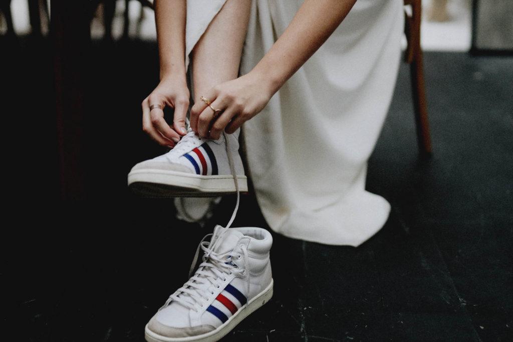 femme en baskets et robe de mariée entrain de lacer ses chaussures festival crazy folk love